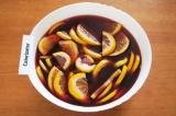 Шаг 5. Залить фрукты вином с водой. Перемешать. Поставить напиток в холодильник