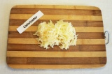 Шаг 4. Яблоко почистить, потереть, сбрызнуть лимонным соком и добавить в салат.