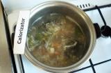 Шаг 5. В уху добавить морковь с луком приправы и специи, варить на среднем огне