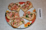 Шаг 5. На каждый кусочек хлеба выложить тертый сыр и колбасную смесь.