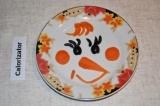 Шаг 7. Для украшения взять морковь и маслины. С моркови вырезать носик, щеки