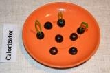 Шаг 5. Маслины разрезать на половинки. Стебельки укропа или петрушки просунуть