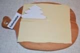 Шаг 1. Слоеное тесто раскатать. Из бумаги вырезать шаблон елочки и по шаблону из