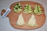 Шаг 5. Сформировать ёлочку: начиная с верха бутерброда, выложить половинки огурч