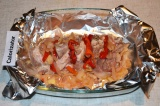 Шаг 4. Противень застелить фольгой и выложить на нее мясо. Разрезы заполнить лук