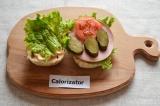Шаг 5. Помидор и огурец нарезать кружочками. Выложить овощи на колбасу.