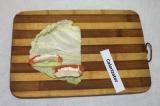 Шаг 5. По длине капустного листа, с одного края, выложить полоски помидора, огур