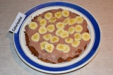 Шаг 8. Первый корж смазать сметанным кремом, сверху выложить кружочки бананов.