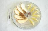 Шаг 6. Выложить на блюдо дольки яблок, кусочки орехов и сыр. По центру высыпать