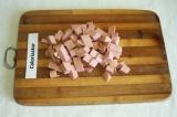 Шаг 2. Кубиками нарезать колбасу.