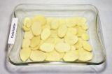 Шаг 8. На дно формы смазанной маслом выложить в один слой картофель. Посолить.