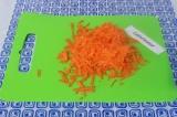 Шаг 3. Натереть морковь на крупной терке и выложить в сковородку к луку. Помешив