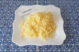 Шаг 2. Натереть сыр на мелкой терке, выложить в тарелку.