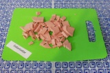 Шаг 4. Нарезать колбасу на кусочки, выложить в сковородку без масла. Жарить, пом