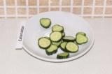 Шаг 10. Нарезать произвольно огурец. Выложить на тарелку салат, бигус и украсить