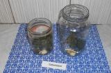 Шаг 1. В стерилизованные банки выложить по 2 зубчика чеснока, листья смородины