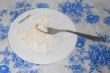 Шаг 1. Творог выложить в тарелку, размять вилкой.