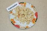 Шаг 1. Хлеб нарезать на маленькие кубики, посолить и поперчить, обжарить на сухо