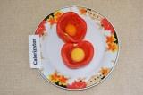 Шаг 2. В каждую половинку помидора добавить сырое яйцо.