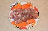 Шаг 2. Очистить морковь и нарезать полукольцами. Добавить к свинине.