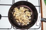 Шаг 4. На сковороду вылить подсолнечное масло, обжарить грибы и лук в течение 4