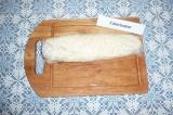Шаг 4. С помощью пищевой пленки свернуть тесто в рулет, края защипать.