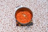 Шаг 4. Добавить к специям морковь и обжаривать еще минуту.