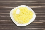 Шаг 3. На плоскую тарелку выложить картофель, натертый на крупной терке, подсоли