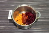 Шаг 5. К специям добавить морковь, свеклу, натертую на терке и томатную пасту.