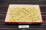 Шаг 8. На дно формы для запекания выложить половину макарон.